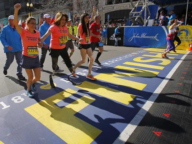 Celeste Corcoran, vítima do atentado de Boston em 2013 quando perdeu as duas pernas, cruza a linha de chegada da maratona com ajuda de familiares nesta segunda (21) (Foto: Brian Snyder/Reuters)