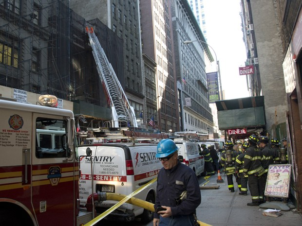 Bombeiros se reúnem em local onde um prédio que estava sendo demolido desabou em Manhattan, NY, na sexta (30) (Foto: AP Photo/Bebeto Matthews)