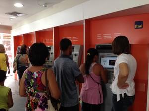 Funcionária do Itaú orienta clientes no caixa de autoatendimento.  (Foto: Natália Souza/G1)
