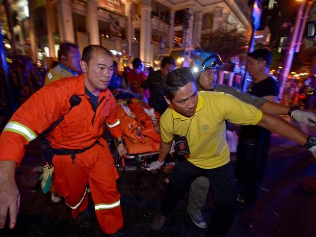 Equipe de resgate socorre um ferido no local onde explodiu uma bomba no centro de Bangcoc, na Tailândia. Uma forte explosão deixou mais de 10 mortos no centro da capital tailandesa (Foto: Pornchai Kittiwongsakul/AFP)