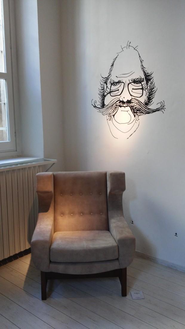 A poltrona Voltaire ao lado de uma caricatura do designer (Foto: Stéphanie Durante/Editora Globo)