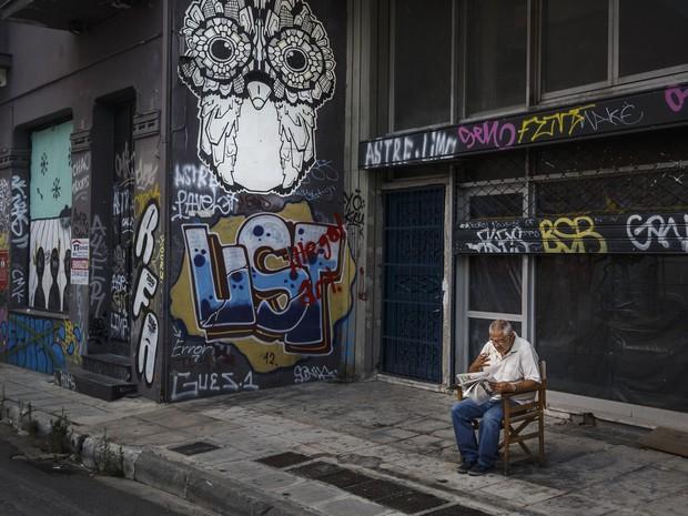 Homem lê jornal em frente a lojas fechadas em Atenas, na Grécia.  (Foto: Daniel Ochoa de Olza / AP)