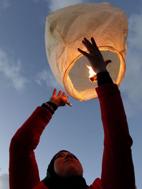 Mulher líbia solta balão em comemoração aos dois anos da revolução que derrubou o ditador Muanmar Kadhafi (Foto: Mohammad Hannon/AP)