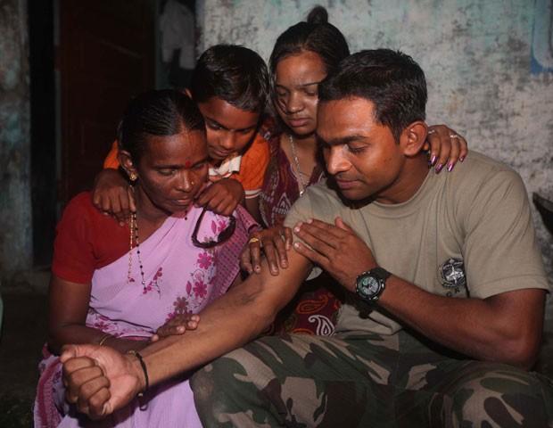 Ganesh Raghunath Dhangade mostra tatuagem que o ajudou a reencontrar sua família para sua mãe e irmãos  (Foto: AFP)