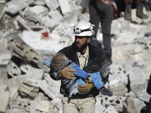 Homem carrega criança em local atingido por bombardeios na província de Idlib, na Síria, que ativistas dizem terem sido feitos por forças russas (Foto: REUTERS/Khalil Ashawi)