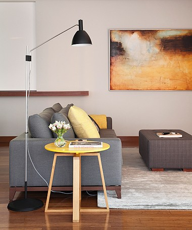 Detalhe da sala de TV, com detalhes em amarelo na mesa lateral, nas almofadas e no quadro na parede (Foto: MCA Estúdio)