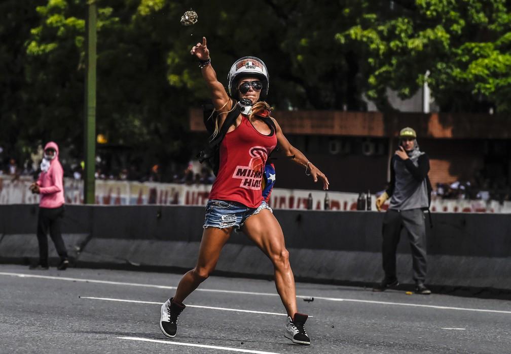 Manifestante que foi comparada à Mulher Maravilha joga pedra em manifestação em Caracas, no dia 1º de maio (Foto: Juan Barreto/AFP)