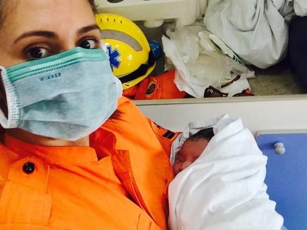 Bombeira segura bebê que nasceu dentro de carro quebrado em Brasília (Foto: Corpo de Bombeiros DF/Divulgação)
