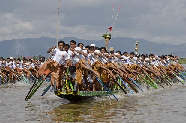 Duas canoas com 64 remadores disputam uma competição de remo durante a festa. A tradição dos pescadores Intha é remar com as pernas e os pés (Foto: Haroldo Castro/ÉPOCA)
