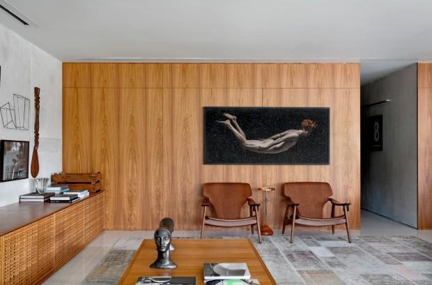 Trabalho do fotógrafo Gabriel Wickbold destaca-se na parede revestida de freijó pela Brumatti Marcenaria. Entre as poltronas de Sergio Rodrigues, há a pequena mesa do Lattoog Design, tudo na Way Design (Foto: Denilson Machado / MCA Estúdio)