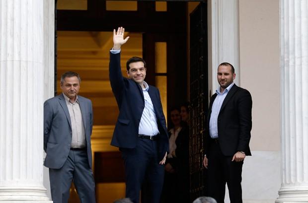 O primeiro-ministro recém-empossado da Grécia, Alexis Tsipras, acena para a imprensa ao chegar a sua residência oficial (Foto: Thanassis Stavrakis/AP)