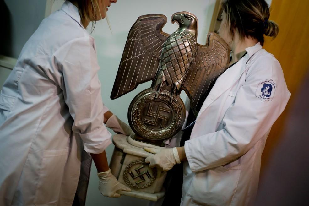 Integrantes da polícia carregam estátua com a suástica encontrada em casa de colecionador na Argentina  (Foto: Natacha Pisarenko/ AP)