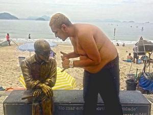 Bin Laden faz o 'hang loose' para a estátua de Drummond em Copacabana (Foto: Reprodução / Facebook do cantor)