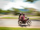 Bebê é transportado entre duas mulheres em motocicleta na capital