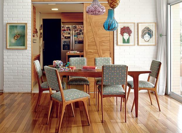A sala de jantar tem móveis dos anos 1950, garimpados em feiras de antiguidades. Na parede de tijolos aparentes, a porta de correr leva à cozinha. Apesar de ser um apartamento, a decoração feita pela moradora Adriana Gama lembra uma casa (Foto: Victor Affaro/Casa e Jardim)
