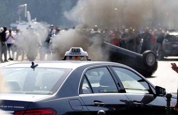 Manifestação de taxistas em junho virou carros do Uber e impediu que motoristas adeptos do aplicativo dirigissem. (Foto: Charles Platiau/Reuters)