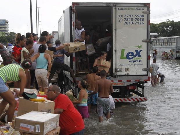 Avenida Brasil completamente alagada em Irajá. Jovens saqueiam caminhão dos frangos. (Foto: Marcelo Carnaval/Agência O Globo)