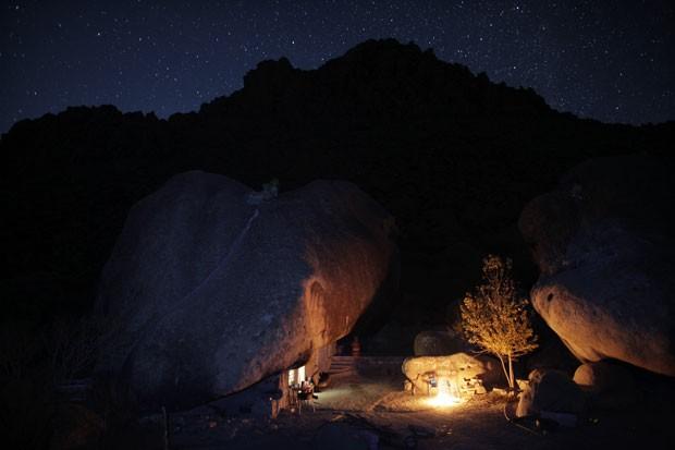 Fogueira ilumina o exterior da casa durante a noite no deserto mexicano (Foto: Daniel Becerril/Reuters)
