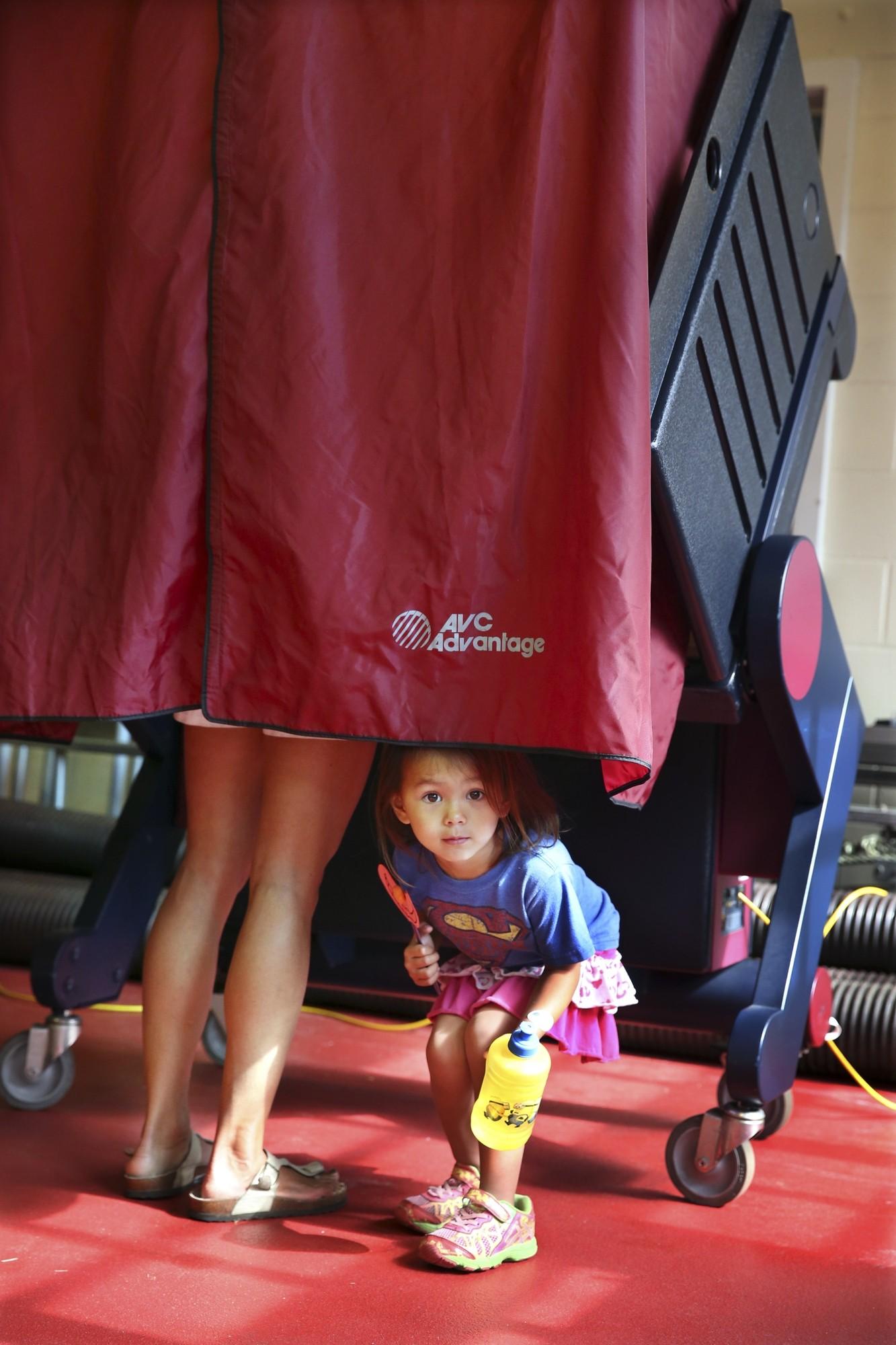 Menina olha por baixo de cortina enquanto a mãe vota nas prévias desta terça em Mendham Township, em Nova Jersey (Foto: Mel Evans/AP)