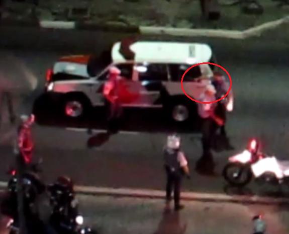 Detalhe mostra braço direito do policial militar quebrando o vidro da viatura: PM diz que não orienta nenhum policial a danificar o patrimônio público (Foto: Reprodução)