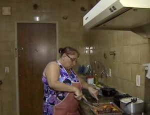 Dona Maria cozinha para os jogadores do São José Basquete na república (Foto: Reprodução/ TV Vanguarda)