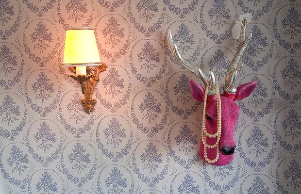 Bijus chiques ou até mesmo joias podem compor a decoração da sala, por exemplo. Aqui, um colar de pérolas faz par com a cabeça de alce. Apartamento do artista plástico Felipe Morozini (Foto: Maíra Acayaba/Casa e Jardim)
