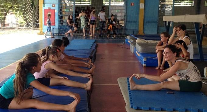 Atletas se alongam (ao fundo, concentração de pessoas) para mais um dia de treinamento (Foto: Divulgação)