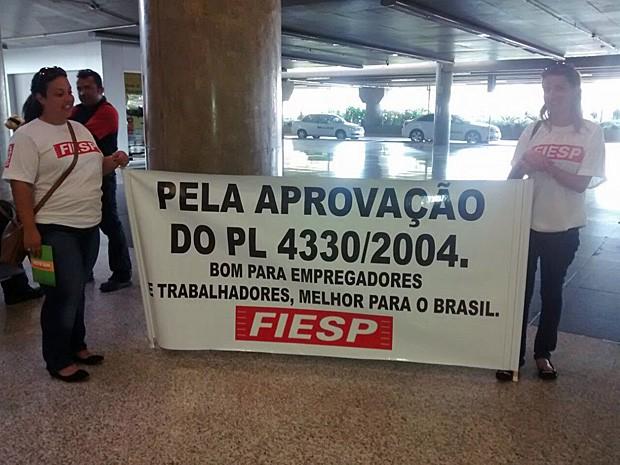 Representantes da Fiesp mostram para passageiros faixa a favor do projeto de lei da terceirização no Aeroporto de Brasília (Foto: Isabella Calzolari/G1)