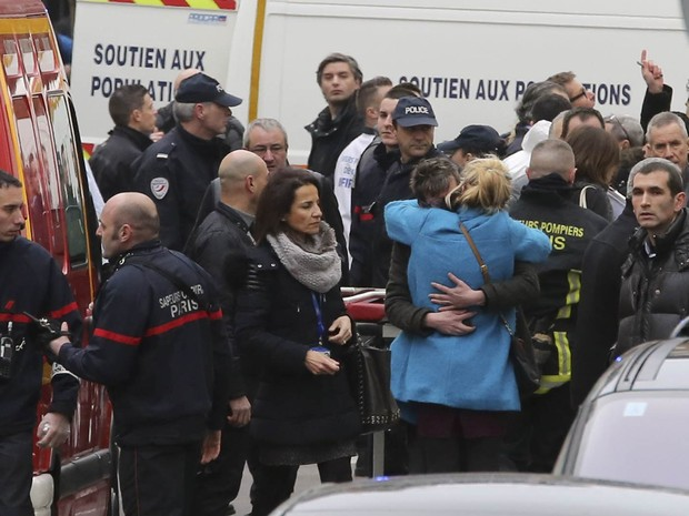 Pessoas se abraçam em frente à sede da revista satírica 'Charlie Hebdo', após ataque terrorista em Paris (Foto: Remy de la Mauviniere/AP)