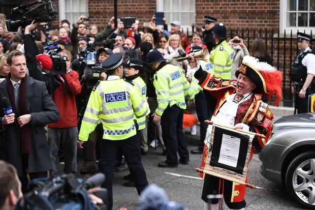 Tony Appleton comemora o nascimento e policiais contém a multidão (Foto: AFP)
