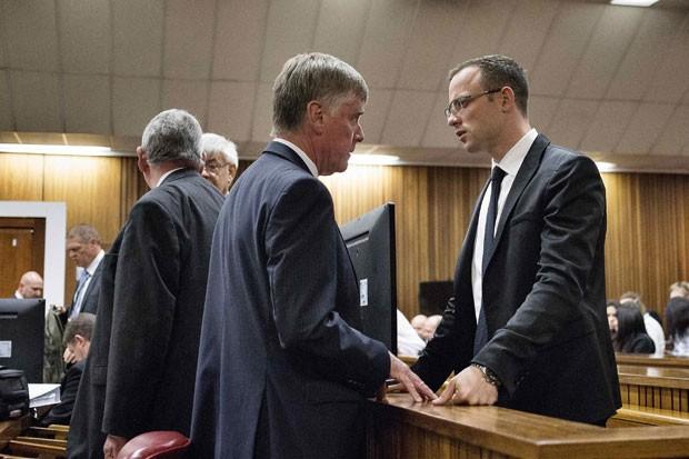 O atleta paralímpico Oscar Pistorius conversa com seus advogados durante seu julgamento nesta segunda-feira (7) em Pretória, na África do Sul (Foto: Themba Hadebe/Reuters)