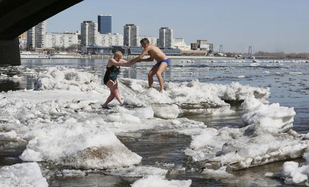 Russos se arriscam ao caminhar sobre os blocos de gelo (Foto: Ilya Naymushin/Reuters)