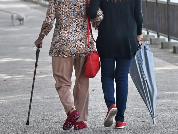 Idosa caminha ao lado de cuidadora em parque em Cingapura nesta quinta-feira (29)  (Foto: Roslan Rahman/AFP)