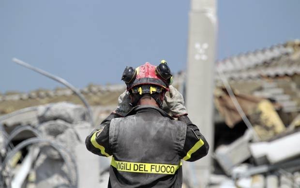 Bombeiro em frente a destroços de prédio destruído pelo terremoto em Medolla, próximo à cidade italiana de Modena, nesta quarta-feira (30) (Foto: AFP)