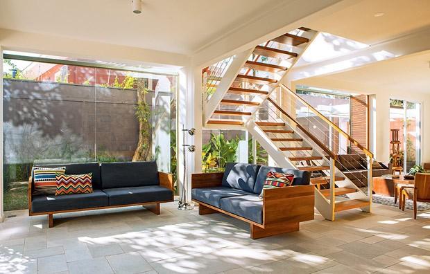 Os arquitetos do escritório Arkitito criaram uma caixa de vidro que avança 80 cm no jardim lateral para aumentar o living. Assim, a casa dos anos 1960 ganhou muito mais iluminação natural. A transparência acompanha a altura da escada (Foto: Edu Castello/Editora Globo)