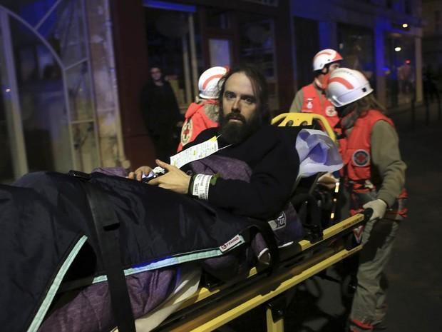 Ferido é retirado de maca da casa de shows Bataclan, local que sofreu ataque terrorista em Paris (Foto: Thibault Camus/AP)