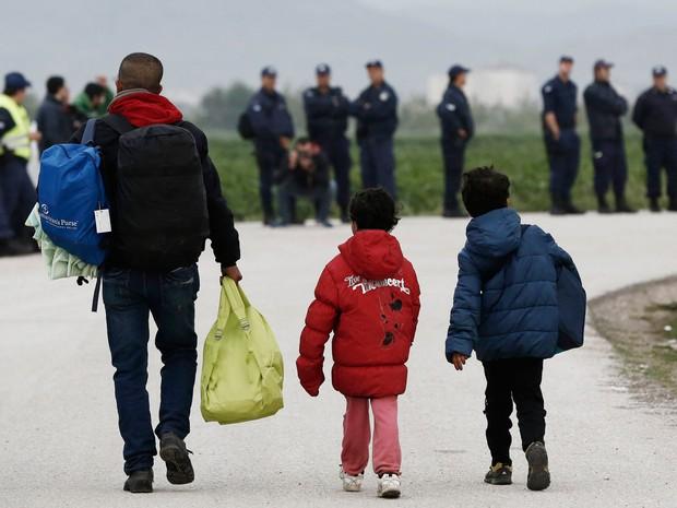 Migrante com seus filhos carrega pertences na saída do campo de Idomeni, em Lesbos, na Grécia (Foto:  Yannis Kolesidis/AFP)