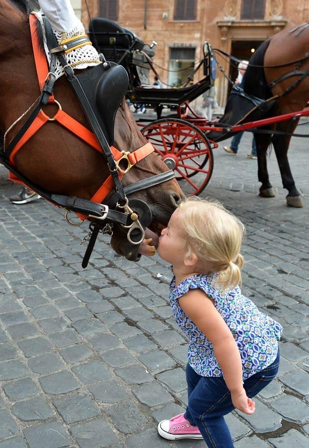 Cavalo reagiu à aproximação da menina, que lhe deu um beijo (Foto: Alberto Pizzoli/AFP)