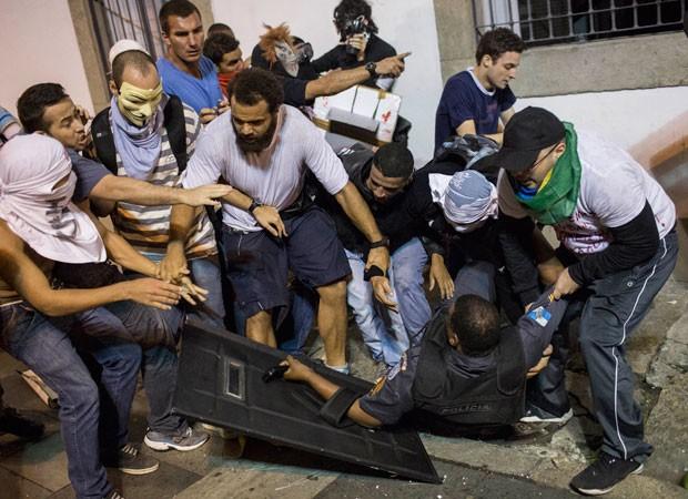 Alguns manifestantes tentam impedir agressão de outros a PM caído na Assembleia Legislaiva do Rio (Foto: Felipe Dana/AP)