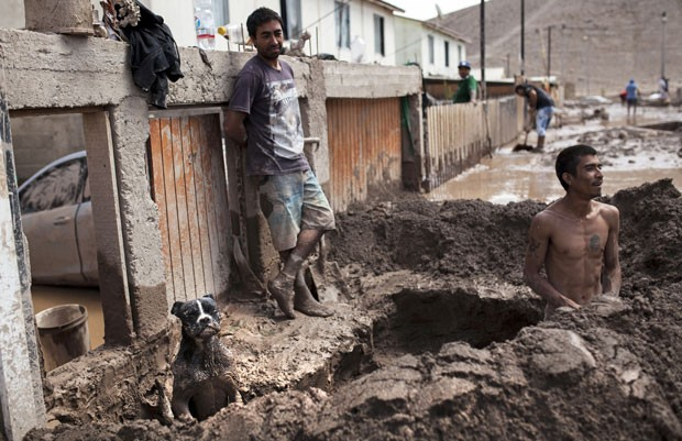 Homens são vistos em meio a lama causada por enchentes no rio Copiapó no norte do Chile nesta segunda-feira (30) (Foto: Patricio Miranda/AFP)
