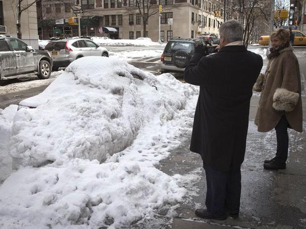 Homem tira fotos de carro que está completamente encoberto de neve e gelo acumulados após recentes tempestades em Manhattan (Foto: Carlo Allegri/Reuters)