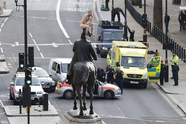 Homem não identificado ficou duas horas nu sobre estátua em Londres nesta sexta-feira (23) (Foto: Justin Tallis/AFP)