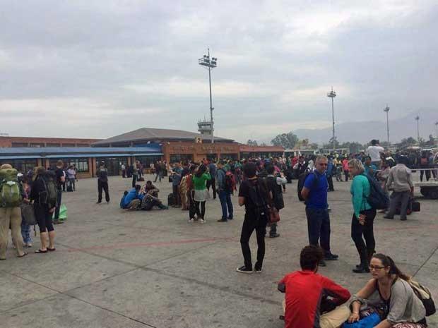 Pessoas esperam do lado de fora do Aeroporto Internacional de Katmandu. (Foto: Dhany Osman / via Reuters)