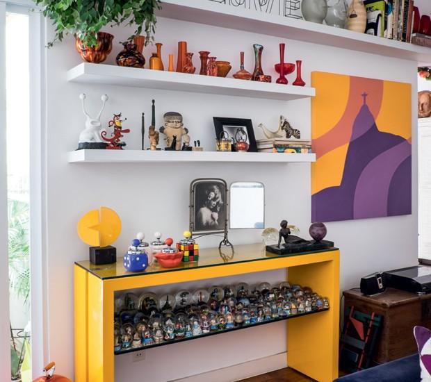 Na estante, coleção de vasos vermelhos trazidos de mercados de rua de vários países, coleção de bolas de neve, miniesculturas, espelho raro e histórias de vida. (Foto: Lufe  Gomes/Life by Lufe)