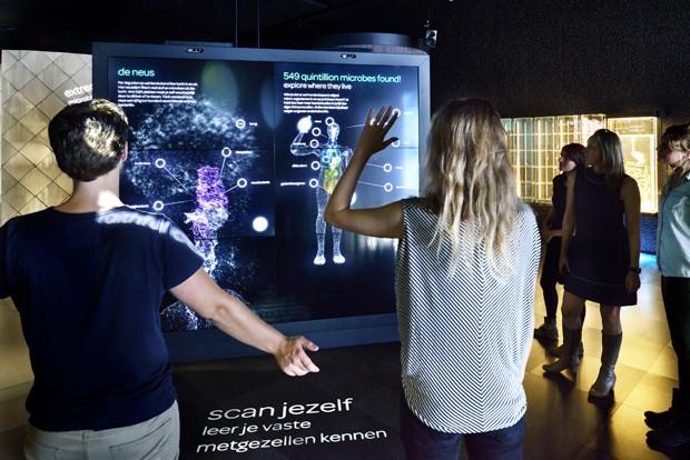 Visitantes passam por 'scanner' que determina quantos micróbios vivem em seu corpo (Foto: AFP Photo/Micropia/Maarten Van Der Wal)