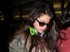 Selena Gomez evita flashes ao deixar aeroporto