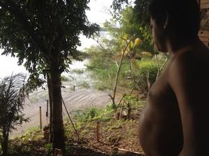 Alex tem três réguas de medição do rio como vizinhas e mora embaixo de barranco (Foto: Ísis Capistrano/ G1)