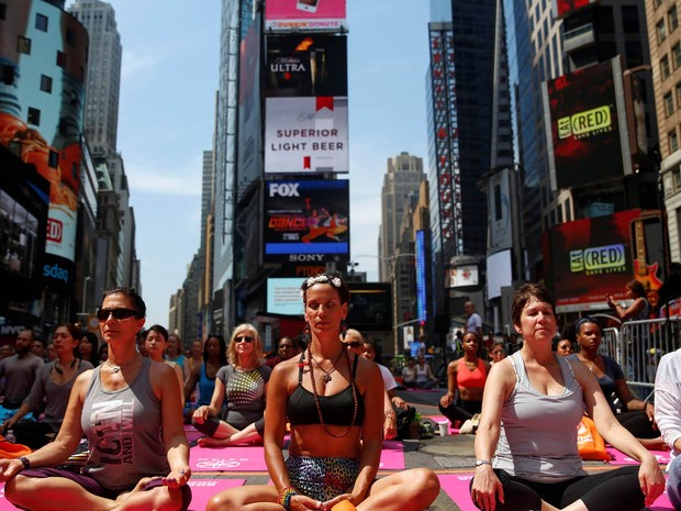 Grupo participa de aula de ioga no meio da Times Square, em Nova York, em evento celebrando o solstício (Foto: Shannon Stapleton/Reuters)