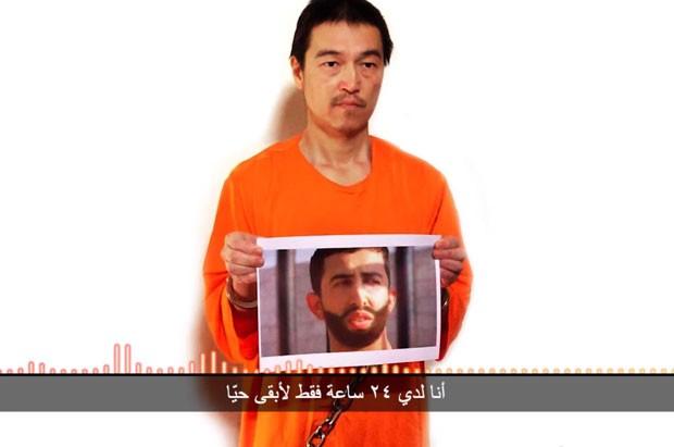 Imagem retirada de vídeo no Youtube publicado nesta terça (27)  em que Kenji Goto aparece segurando uma foto do que parece ser o piloto  Mu'ath al-Kaseasbeh (Foto: AP)