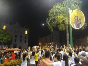 Fieis erguemas as mãos no momento da chegada da Berlinda à Praça Frei Caetano Brandão. (Foto: Dominik Giusti/ G1)